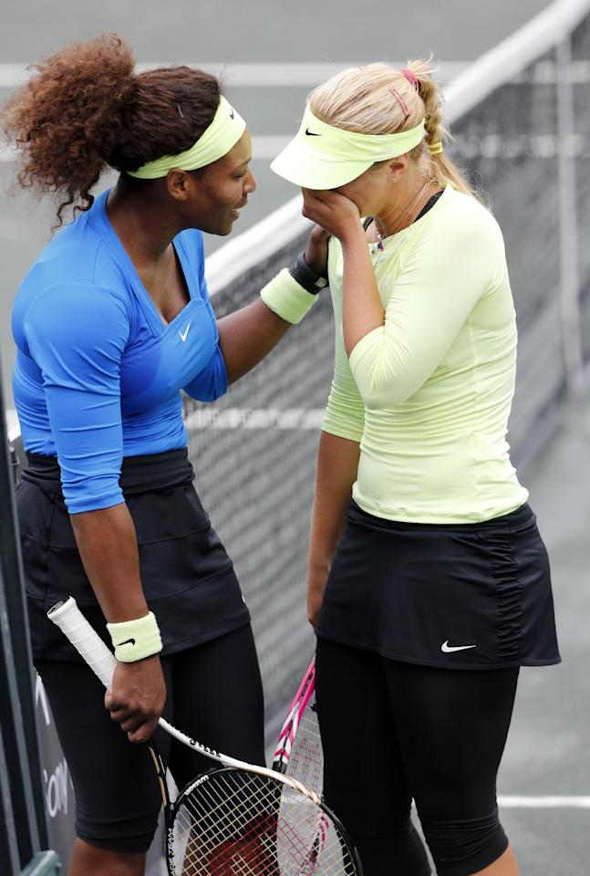 Serena Williams, at left, consoles Sabine Lisicki, of Germany, after Lisicki had to withdraw from their quarterfinals match due to a sprained ankle at the Family Circle Cup tennis tournament in Charleston, S.C., Friday, April 6, 2012. (AP Photo/Mic Smith)