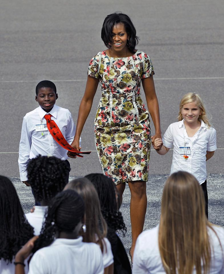 Photo by: (AP Photo/Chris O'Meara)<br />Michelle Obama at Tampa International Airport in Tampa, Fla., Oct. 27, 2011.-<br />First Lady Michelle Obama escorts John Sexton Elementary School students ,William Porter, left, and Breann Rouse across the tarmac at Tampa International Airport in Tampa, Fla., Thursday, Oct. 27, 2011. The St. Petersburg, Fla., school received an award from the Alliance for a Healthier Generation, one of only five schools to receive the 2010-2011 award and the only school to receive the silver award. Mrs Obama stopped to greet the students on the way to a Democratic fundraiser.