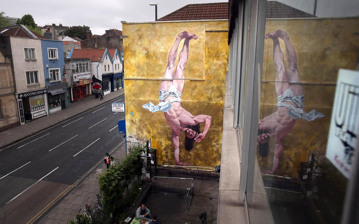 General view of Cosmo Sarson's mural of Jesus breakdancing that he has painted on the 8.5 metre wall beside The Canteen in Stokes Croft and is being officially unveiled this evening is reflected in a window, on June 11, 2012 in Bristol, England. The artist was commissioned by The Canteen to paint the wall, which is directly opposite Banksy's Mild Mild West. The controversial 'Breakdancing Jesus', which took 4 days to paint and involved a kilo of glitter and was inspired by an actual event in the Vatican where breakdancers performed to an applauding Pope John Paul II in 2004, is likely to be the latest attraction for graffiti tourists visiting Bristol, often seen the spiritual home of underground artist Banksy. (Photo by Matt Cardy/Getty Images)