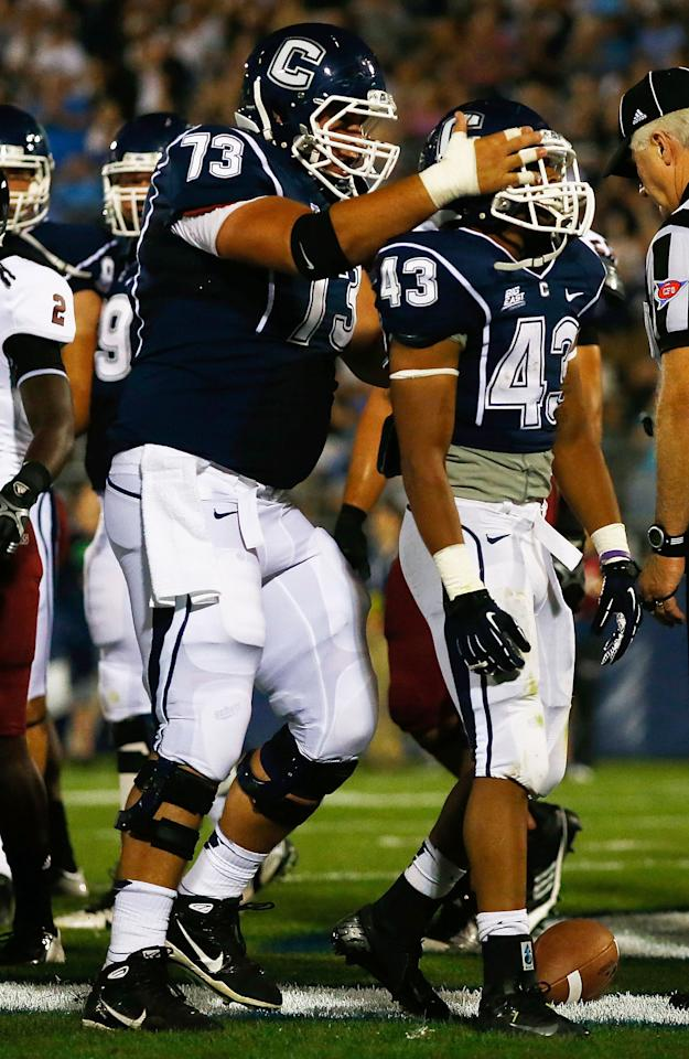 EAST HARTFORD, CT - AUGUST 30: Lyle McCombs #43 of the Univeristy of Connecticut Huskies is congratulated by teammate Alex Mateas #73 after scoring a touchdown in the first quarter against the University of Massachusetts Minutemen during the game on August 30, 2012 at Rentschler Field in East Hartford, Connecticut.  (Photo by Jared Wickerham/Getty Images)