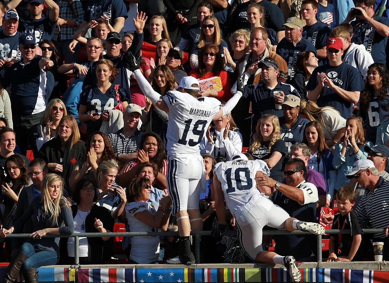 DALLAS, TX - DECEMBER 30:  Matt Marshall #19 and JJ Di Luigi #10 of the Brigham Young Cougars celebrate a 24-21 win against the Tulsa Golden Hurricane during the Bell Helicopter Armed Forces Bowl at Gerald J. Ford Stadium on December 30, 2011 in Dallas, Texas.  (Photo by Ronald Martinez/Getty Images)