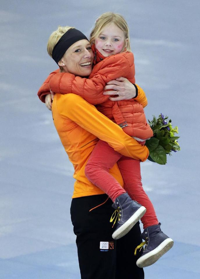Bronze medallist Carien Kleibeuker of the Netherlands poses for photographers carrying her daughter Annemijn during the flower ceremony for the women's 5,000-meter speedskating race at the Adler Arena Skating Center during the 2014 Winter Olympics in Sochi, Russia, Wednesday, Feb. 19, 2014. (AP Photo/Matt Dunham)