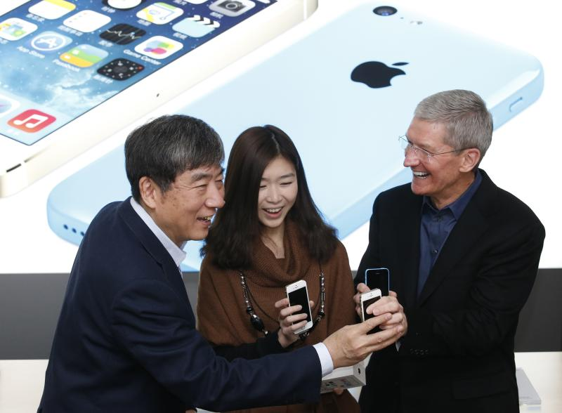 Apple Inc. CEO Tim Cook and China Mobile's Chairman Xi Guohua pose with a customer at an event celebrating the launch of Apple's iPhone on China Mobile's network in Beijing