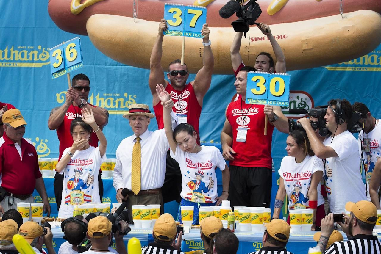 Sonya Thomas, center, wins the Nathan's Famous Fourth of July International Hot Dog Eating contest alongside Juliet Lee, left, and Michelle Lesco, right, at Coney Island, Thursday, July 4, 2013, in the Brooklyn borough of New York. (AP Photo/John Minchillo)