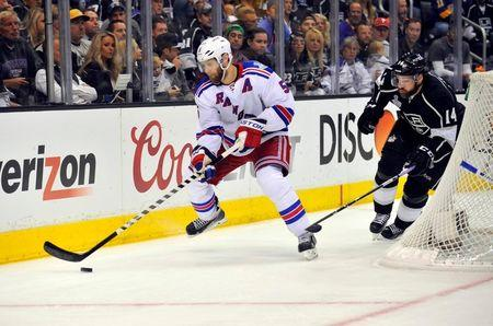 Jun 7, 2014; Los Angeles, CA, USA; New York Rangers defenseman Dan Girardi (5) controls the puck against Los Angeles Kings right wing Justin Williams (14) in the third period during game two of the 2014 Stanley Cup Final at Staples Center. Mandatory Credit: Gary A. Vasquez-USA TODAY Sports