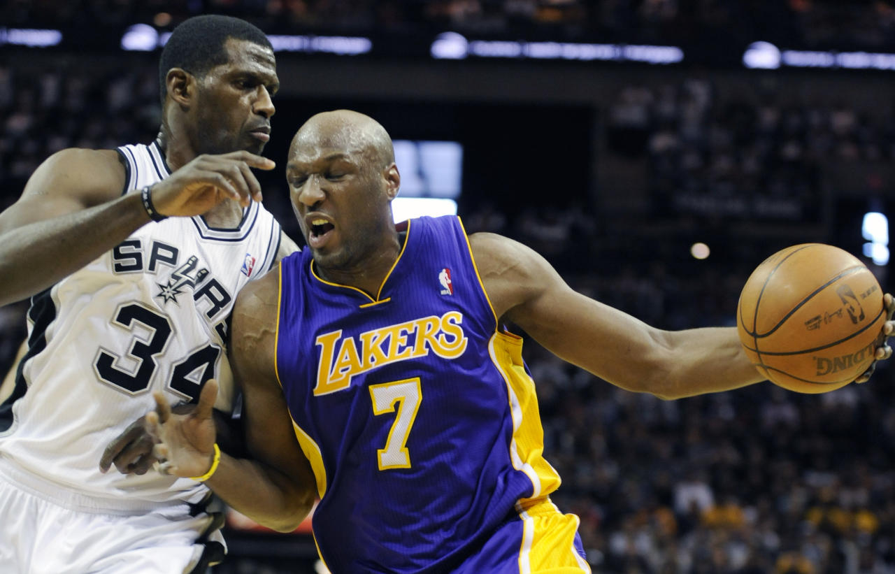 Los Angeles Lakers forward Lamar Odom, right, drives against San Antonio Spurs forward Antonio McDyess during the first half of an NBA basketball game in San Antonio, Sunday, March 6, 2011.