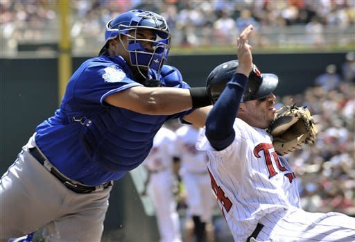 Kansas City Royals' Brayan Pena, left, dives to tag out Minnesota Twins' Trevor Plouffe as Plouffe tried to score from third after Brian Dozier popped out in the third inning in the first baseball game of a doubleheader, Saturday, June 30, 2012, in Minneapolis. (AP Photo/Jim Mone)