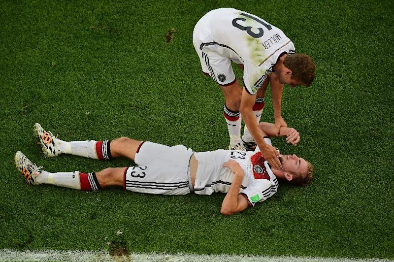 Germany's Christoph Kramer lies on the pitch as teammate Thomas Mueller assists him, during the World Cup final soccer match between Germany and Argentina at the Maracana Stadium in Rio de Janeiro, Brazil, Sunday, July 13, 2014