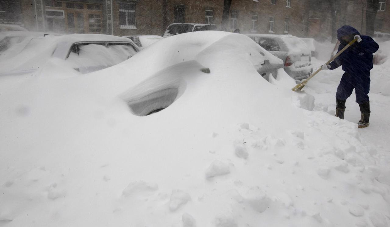 A driver shovels snow off his vehicle in Kiev, Ukraine, Saturday, March 23, 2013. Heavy snow storms from the Balkan region have hit Ukraine since last afternoon, in a last attack by winter at the end of the first spring month. The temperature in the Ukrainian capital is about -8 Celsius (18 F) on Saturday.(AP Photo/Sergei Chuzavkov)