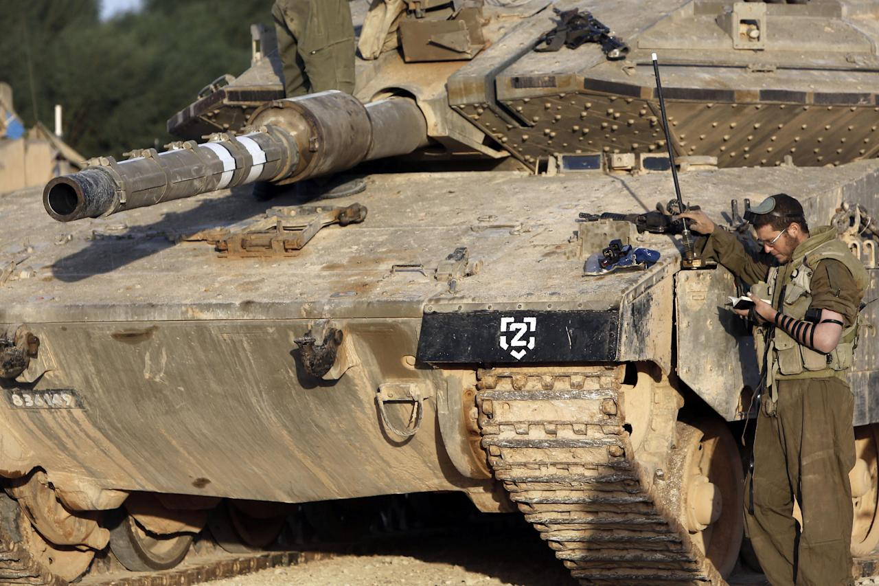An Israeli soldier prays next to a tank along the Israel Gaza border in southern Israel, Sunday, Nov. 18, 2012. Israeli strikes hit two media centers in the Gaza Strip on Sunday, as Israel warned it was widening its range of targets to go after military commanders of the territory's Hamas rulers. (AP Photo/Tsafrir Abayov)