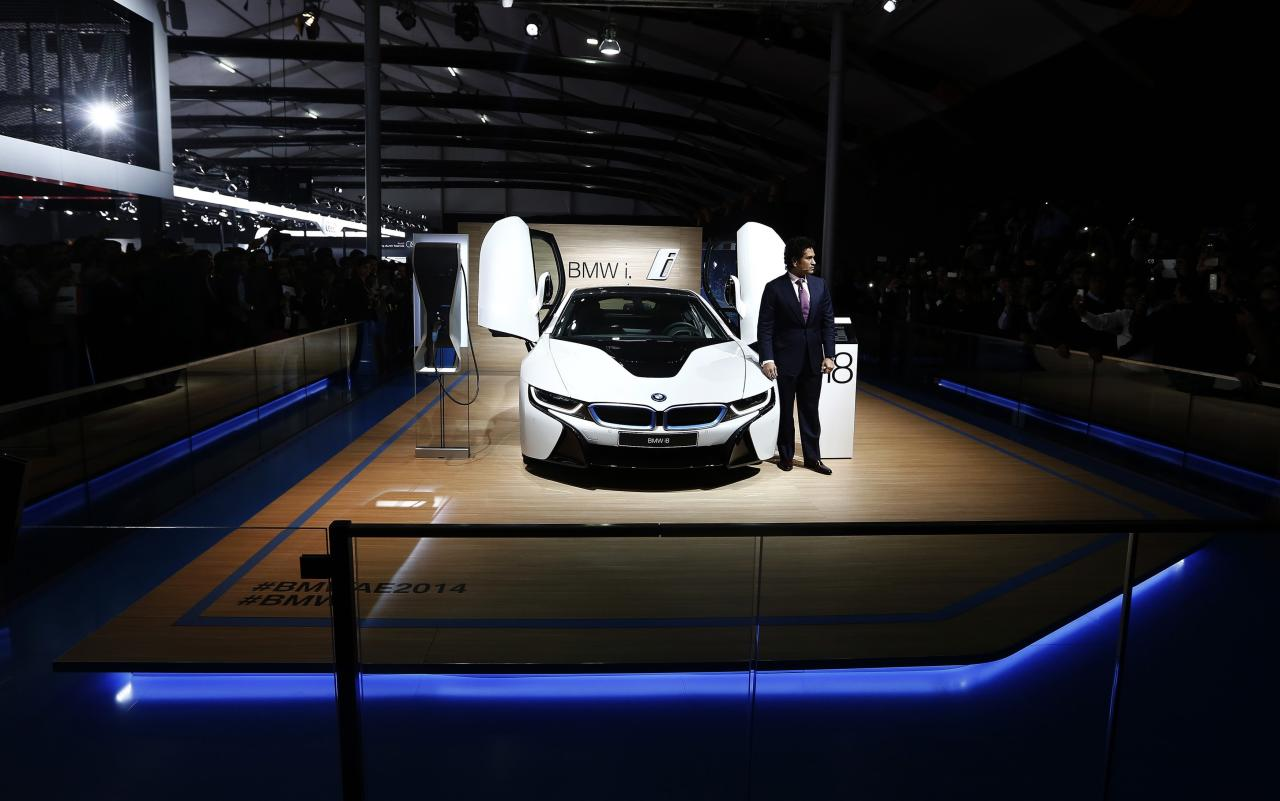Retired cricketer Sachin Tendulkar poses with BMW's i8 hybrid car during its launch at the Indian Auto Expo in Greater Noida, on the outskirts of New Delhi, February 5, 2014. REUTERS/Adnan Abidi (INDIA - Tags: BUSINESS TRANSPORT SPORT CRICKET)