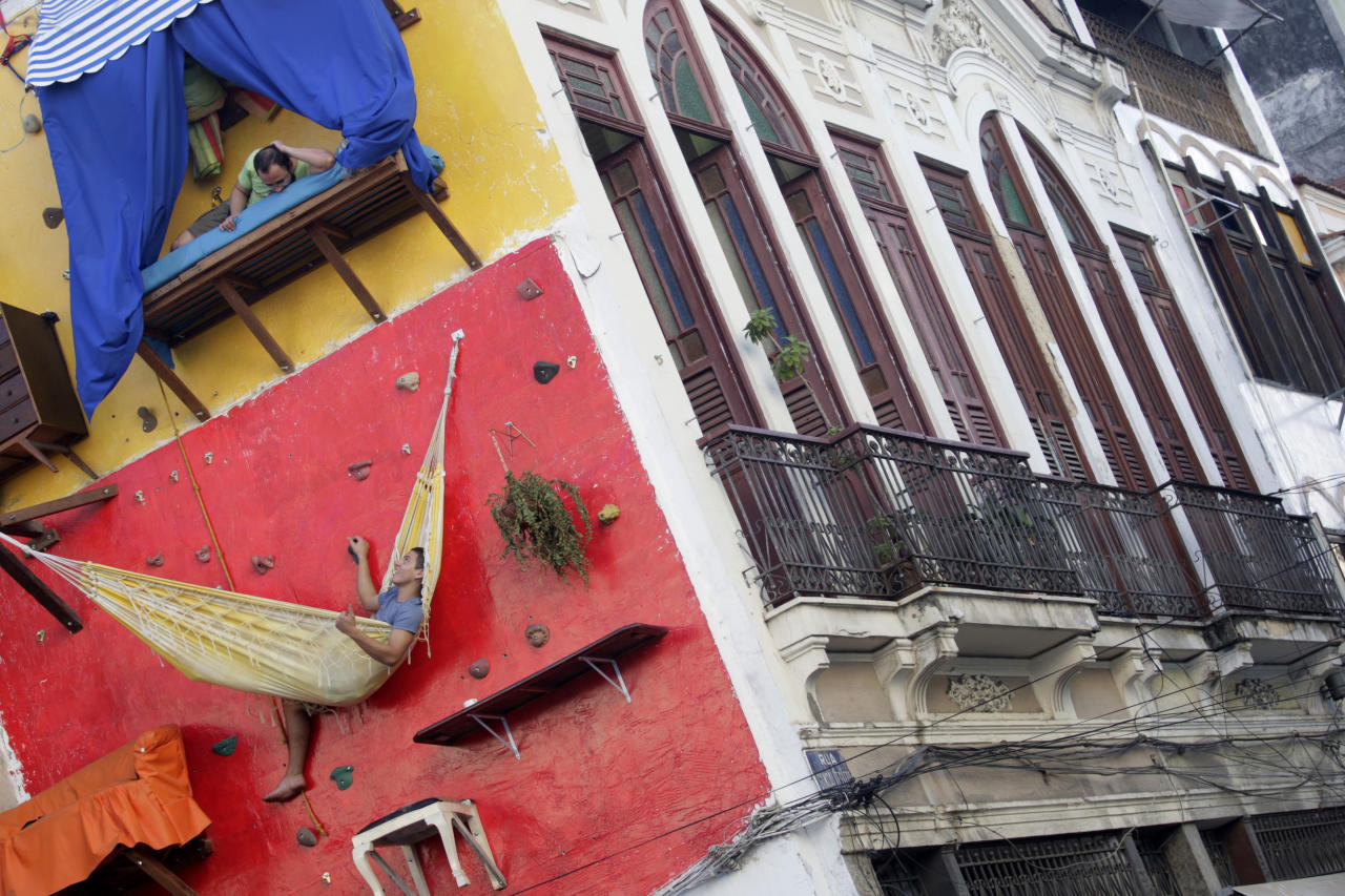 """Brazilian artists Tiago Primo (top) and his brother Gabriel hang out at a wall in Rio de Janeiro July 8, 2009. The bizarre vertical """"house"""" built on a climbing wall by Brazilian artists has been drawing the attention of thousands who walk by the installation in Rio de Janeiro's downtown neighbourhood. REUTERS/Bruno Domingos (BRAZIL SPORT SOCIETY)  FOR BEST QUALITY IMAGE ALSO SEE: GM1E59F1QI101 - RTR25GTH"""