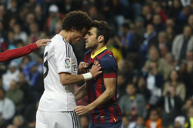 Real's Pepe, left, reacts with Barcelona's Cesc Fabregas, right, as Fabregas celebrated Lionel Messi's goal, during a Spanish La Liga soccer match between Real Madrid and FC Barcelona at the Santiago Bernabeu  stadium in Madrid, Spain, Sunday, March 23, 2014