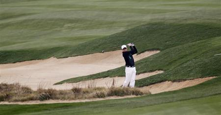 Simon Dyson of Britain hits out of a sand trap on the seventh hole during the BMW Masters 2013 golf tournament in Shanghai