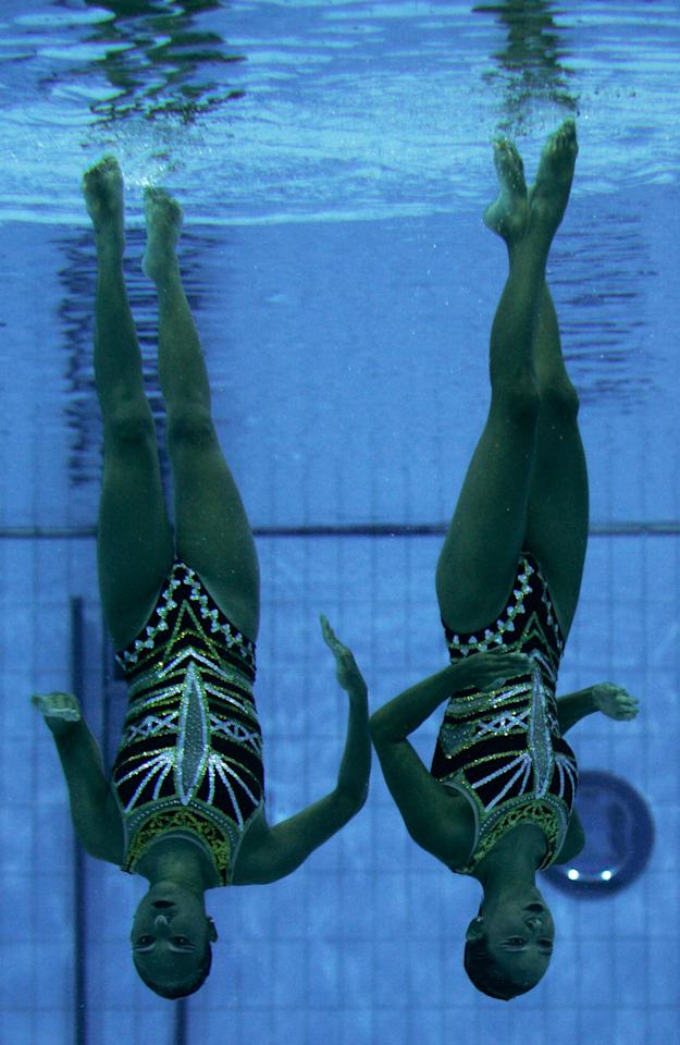 Korea's Kim Sung Eun and Yoo Na Mi perform in the duet technical routine preliminary round in synchronized swimming, in the Olympic Aquatic Center at the 2004 Olympic Games in Athens, Tuesday Aug. 24, 2004. (AP Photo/Lefteris Pitarakis)