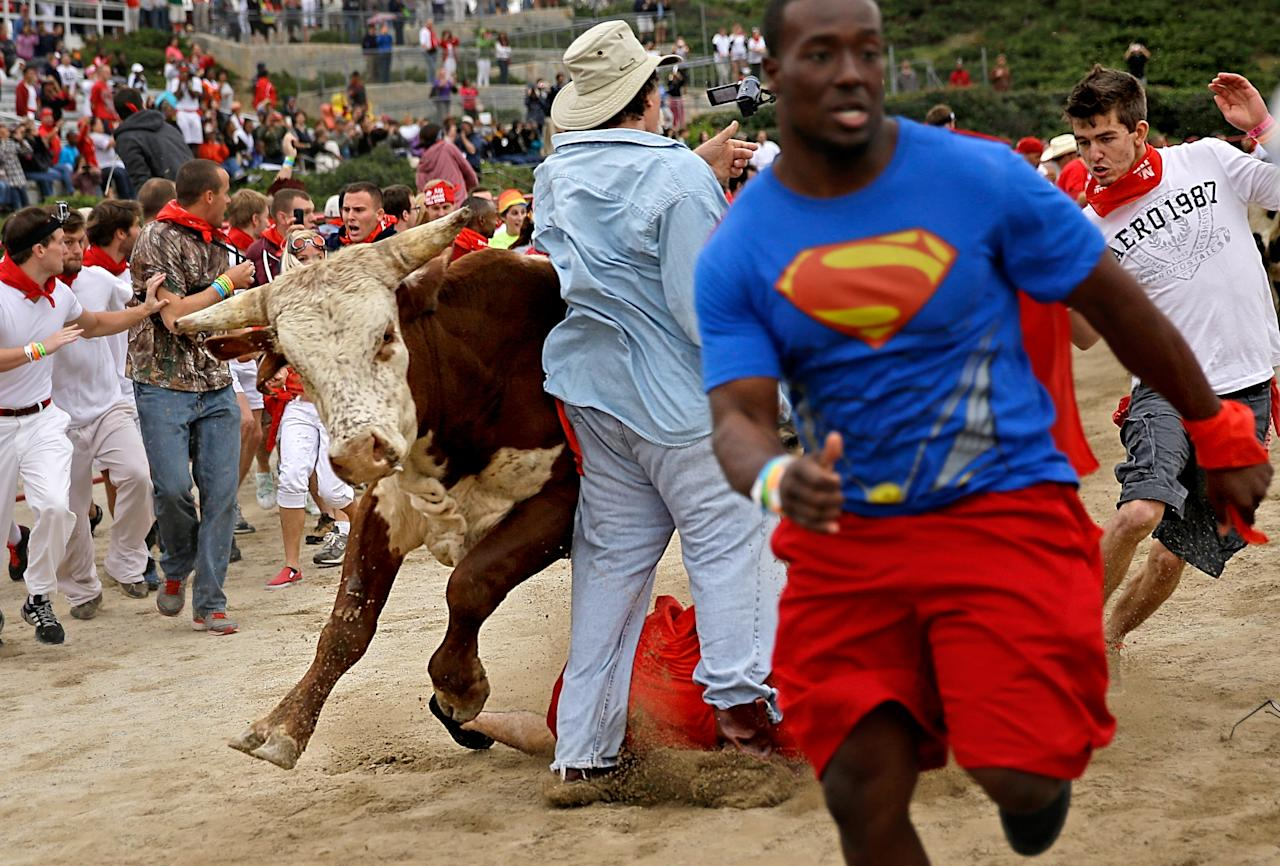 Participants are knocked over by charging bulls during the Great Bull Run at the Georgia International Horse Park, Saturday, Oct. 19, 2013, in Conyers, Ga. The event, expected to attract 3,000 runners Saturday, is inspired by the annual running of the bulls in Pamplona, Spain and has future stops planned in Texas, Florida, California, Illinois and Pennsylvania. (AP Photo/David Goldman)