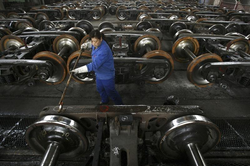 A labourer paints antirust oil on vehicle at a factory in Wuhan