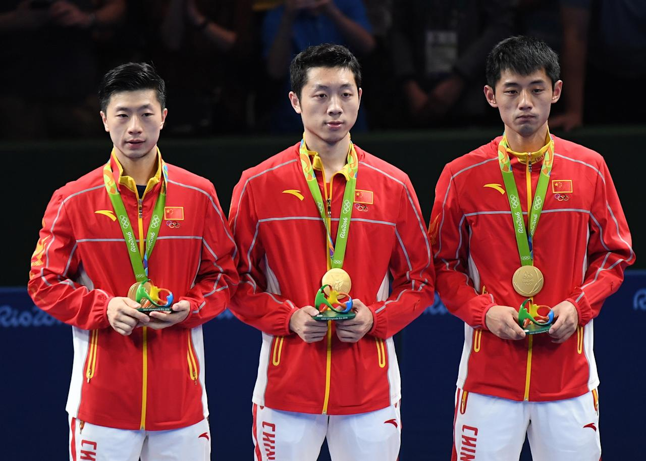<p>(L-R) Gold medalists Ma Long, Xu Xin, Zhang Jike of China pose on the podium during the medal ceremony for the Men's Team Table Tennis on Day 12 of the Rio 2016 Olympic Games at Riocentro – Pavilion 3 on August 17, 2016 in Rio de Janeiro, Brazil. (Photo by VCG/VCG via Getty Images) </p>