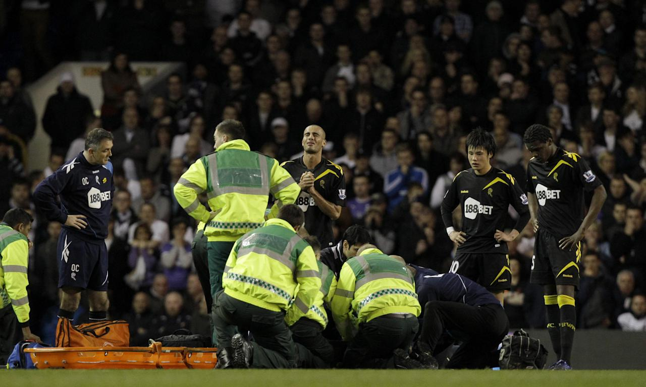 Bolton Wanderers' Fabrice Muamba is obscured by medical staff trying to resuscitate him after collapsing watched by his manager Owen Coyle, left, and then from left teammates Darren Pratley, Ryo Miyaichi and Dedryck Boyata during the English FA Cup quarterfinal soccer match between Tottenham Hotspur and Bolton Wanderers at White Hart Lane stadium in London, Saturday, March 17, 2012. Bolton midfielder Fabrice Muamba has been carried off the field at Tottenham after medics appeared to be trying to resuscitate him during an FA Cup quarterfinal that was abandoned. Muamba went to the ground in the 41st minute with no players around him and the game was immediately stopped. (AP Photo/Matt Dunham)