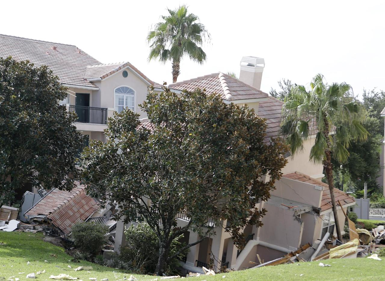 A portion of a building rests in a sinkhole Monday, Aug. 12, 2013 in Clermont, Fla. The sinkhole, 40 to 50 feet in diameter, opened up overnight and damaged three buildings at the Summer Bay Resort. (AP Photo/John Raoux)