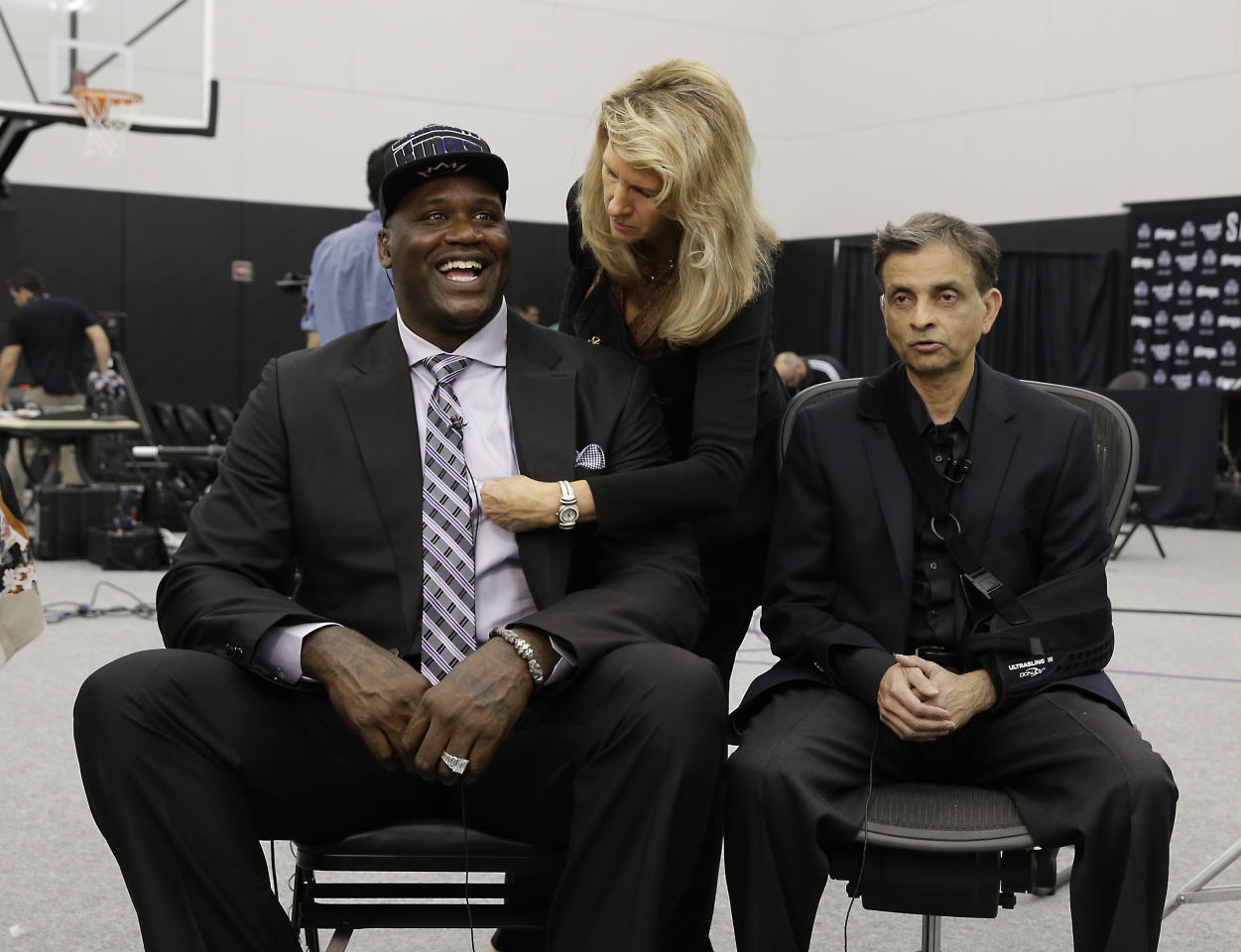 Shaquille O'Neal smiles as makeup artist Jeanne Marie straightens his shirt before a television interview with Sacramento Kings majority owner Vivek Ranadive, right, in Sacramento, Calif., Tuesday, Sept. 24, 2013. O'Neal apologized to all Sacramento Kings fans for his verbal jabs during his playing career and is promising to restore the franchise to its winning ways as a minority owner. (AP Photo/Rich Pedroncelli)