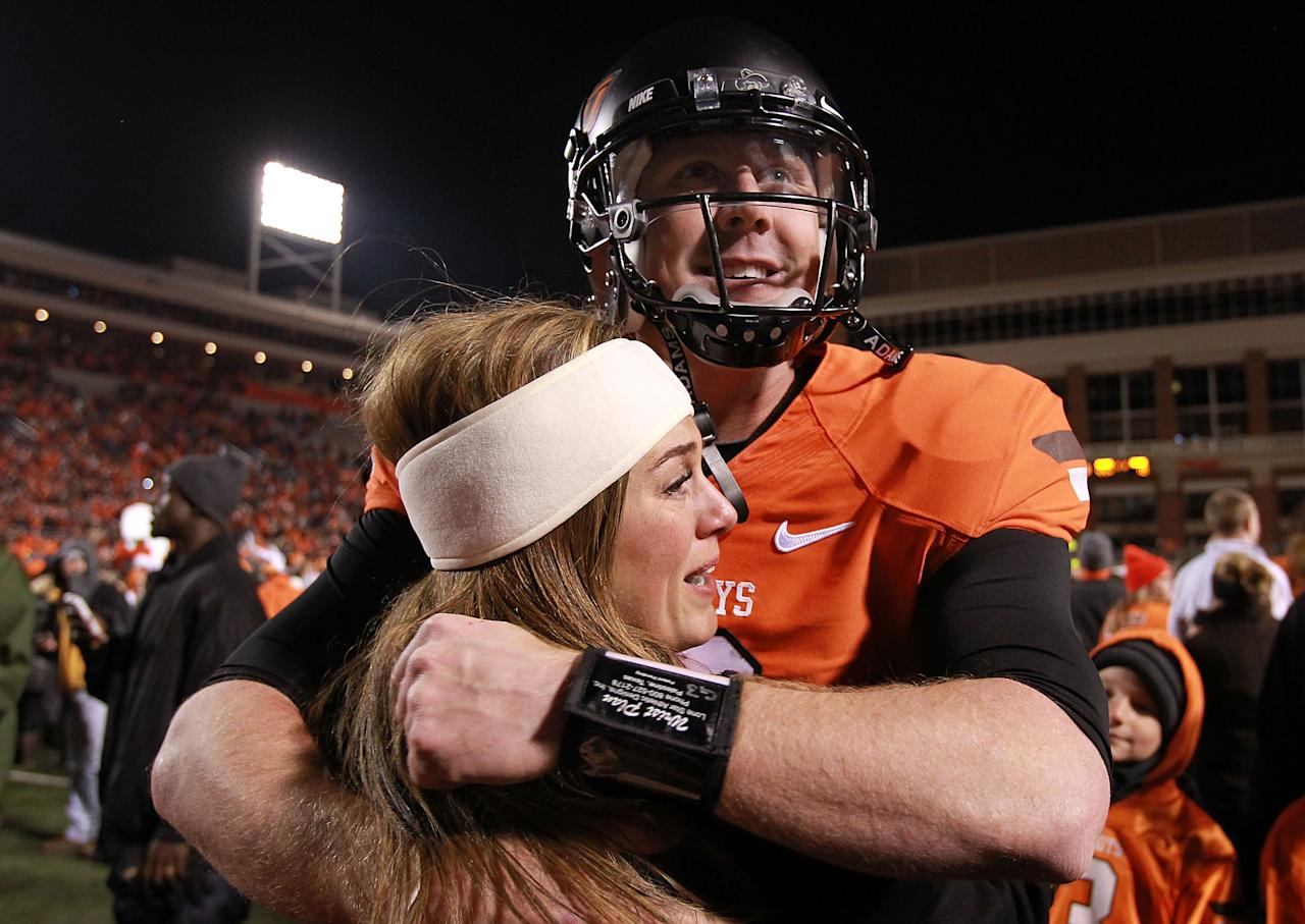 STILLWATER, OK - DECEMBER 03:  Brandon Weeden #3 of the Oklahoma State Cowboys hugs his wife, Melanie Weeden after a 44-10 win against the Oklahoma Sooners at Boone Pickens Stadium on December 3, 2011 in Stillwater, Oklahoma.  (Photo by Ronald Martinez/Getty Images)