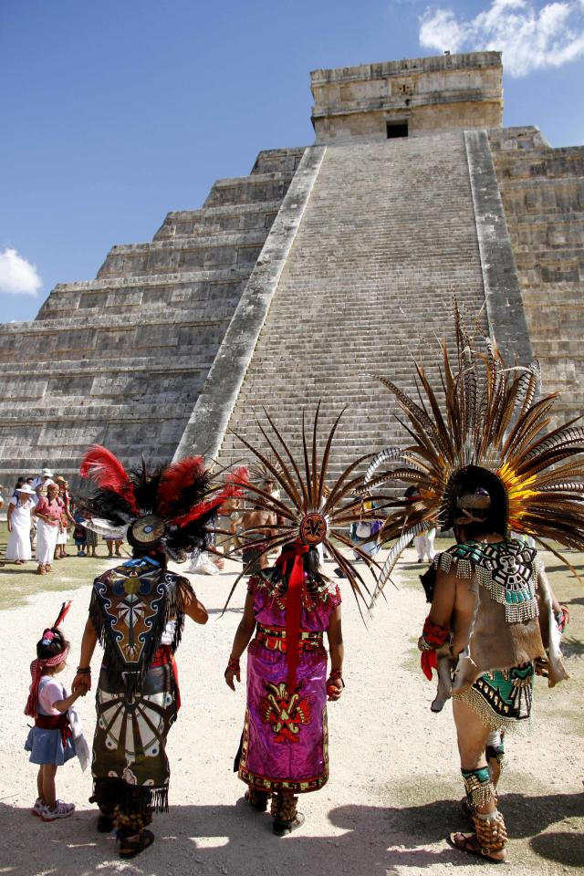 "Mayan gather in front of the Kukulkan Pyramid in Chichen Itza, Mexico, Thursday, Dec. 20, 2012. A Mexican Indian seer who calls himself Ac Tah, and who has traveled around Mexico erecting small pyramids he calls ""neurological circuits,"" said he holds high hopes for Dec. 21. ""We are preparing ourselves to receive a huge magnetic field straight from the center of the galaxy,"" he said. (AP Photo/Israel Leal)"