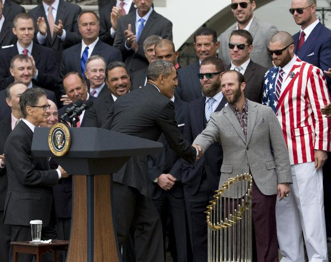 President Barack Obama, shakes hands with Boston Red Sox second baseman Dustin Pedroia, during a ceremony on the South Lawn of the White House in Washington, Tuesday, April 1, 2014, where the president honored the 2013 World Series baseball champion Boston Red Sox. Outfielder Jonny Gomes, sporting an American flag jacket is at right.  (AP Photo/Manuel Balce Ceneta)