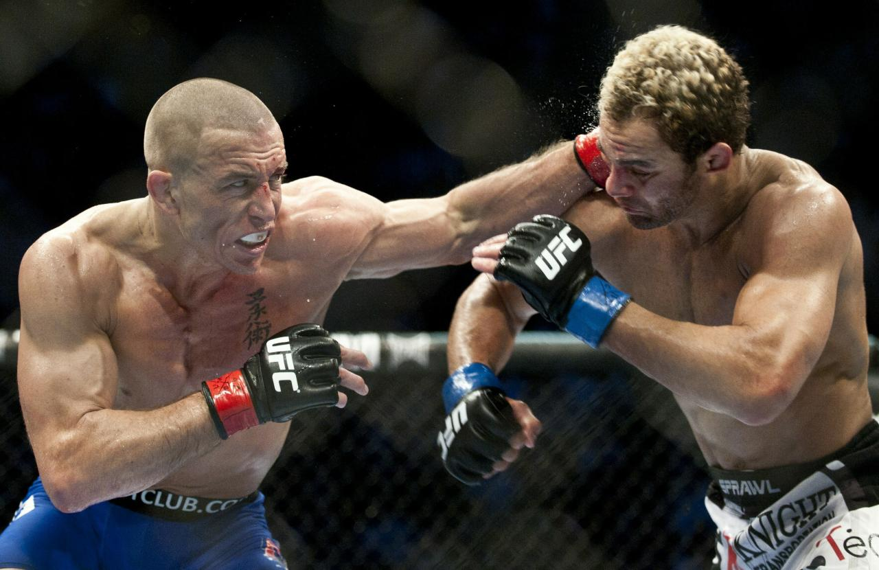 Georges St-Pierre (L) from Montreal, Canada punches Josh Koscheck from Waynesburg US during the third round of the Ultimate Fighting Championship on December 11, 2010 at Bell Centre in Montreal, Quebec, Canada.    AFP PHOTO / ROGERIO BARBOSA (Photo credit should read ROGERIO BARBOSA/AFP/Getty Images)