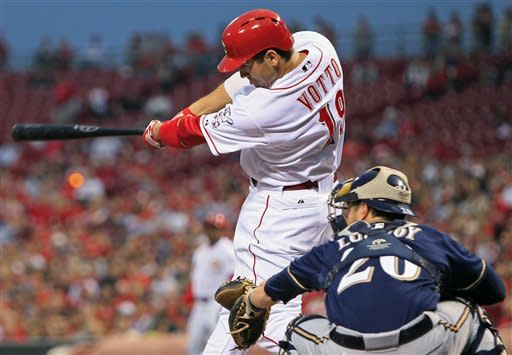 Cincinnati Reds' Joey Votto hits an RBI double during the first inning of a baseball game against the Milwaukee Brewers, Wednesday, Sept. 26, 2012, in Cincinnati. Jonathan Lucroy catches at right. (AP Photo/Al Behrman)