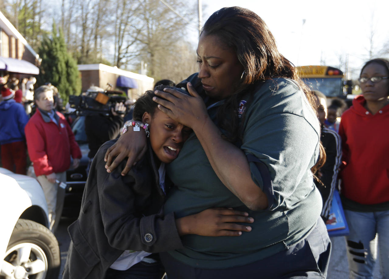 A woman comforts a child after after a shooting at an Price Middle school in Atlanta on Thursday, Jan. 31, 2013. A 14-year-old boy was wounded outside the school Thursday afternoon and a fellow student was in custody as a suspect, authorities said. No other students were hurt. (AP Photo/John Bazemore)