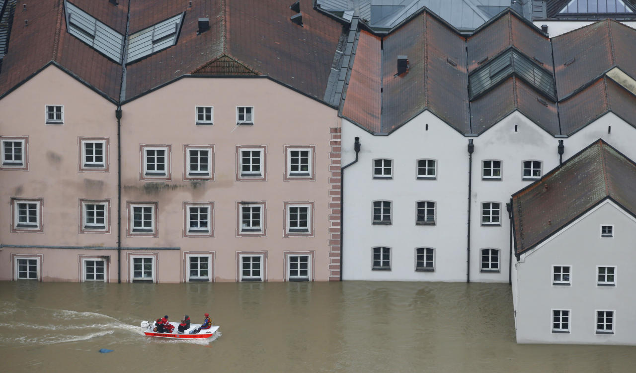 """Members of the Red Cross make their way by boats in the flooded street in the center of Passau, southern Germany, Monday, June 3, 2013. Raging waters from three rivers have flooded large parts of the southeast German city following days of heavy rainfall in central Europe. A spokesman for the city's crisis center said Monday that the situation was """"extremely dramatic"""" and waters are expected to rise further by midday to their level highest in 70 years. (AP Photo/Matthias Schrader)"""