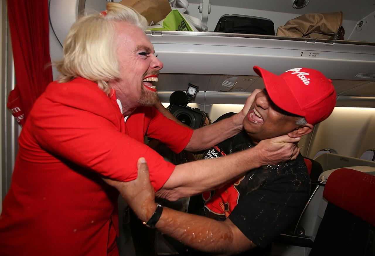 PERTH, AUSTRALIA - MAY 12:  Sir Richard Branson hugs Tony Fernandes after spilling a tray of drinks on him before their flight to Kuala Lumpur at Perth International Airport on May 12, 2013 in Perth, Australia. Sir Richard Branson lost a friendly bet to AirAsia Group Chief Executive Officer Tony Fernandez after wagering on which of their Formula One racing teams would finish ahead of each other in their debut season of the 2010 Formula One Grand Prix in Abu Dhabi and that the loser would serve as a female flight attendant on board the winner's airline.  (Photo by Paul Kane/Getty Images)