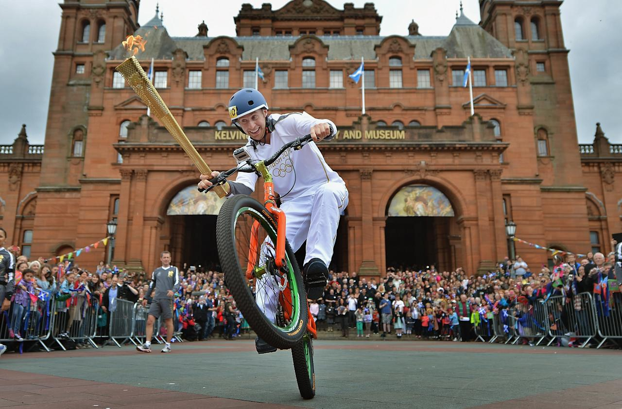 Stunt cyclist Danny MacAskill rides with the Olympic Torch outside Kelvingrove Art Grove Art Gallery during the leg between Stranrear and Glasgow on June 8, 2012 in Glasgow, Scotland. The Olympic torch arrived in Scotland last night to begin its tour of Scotland. The Olympic Flame is now on day 21 of a 70-day relay involving 8,000 torchbearers covering 8,000 miles. (Photo by Jeff J Mitchell/Getty Images)