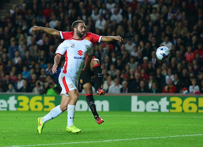 MK Dons Northern Irish striker Will Grigg scores their second goal during the English League Cup second round football match between Milton Keynes Dons and Manchester United at Stadium MK in Milton Keynes, north of London, on August 26, 2014