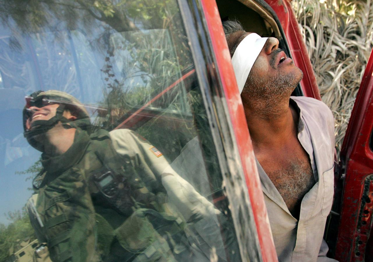 An Iraqi man suspected of having explosives in his car is held after being arrested by the U.S army near Baquba, Iraq, October 15, 2005. [Iraqis headed to the polls in an historic referendum on Saturday, with up to 15 million eligible voters deciding on a controversial new post-Saddam Hussein constitution that its backers hope will unite the torn country. Amid intense security, including a ban on all traffic, voters flowed on foot to polling stations across Baghdad. ]