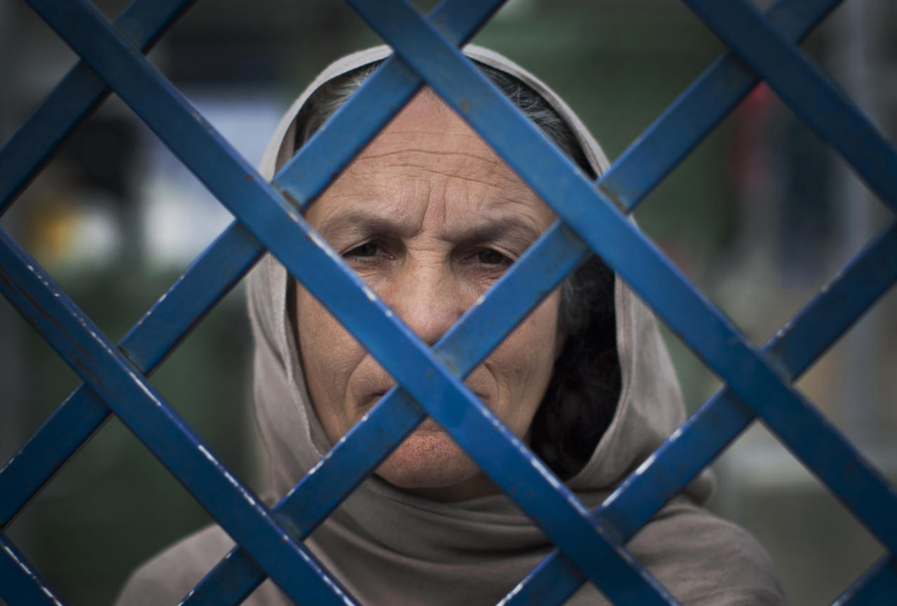 "Picture taken March 28, 2013 shows Afghan female prisoner Fauzia steering out of the prison bars at Badam Bagh, Afghanistan's central women's prison, in Kabul, Afghanistan. Fauzia is the oldest woman in jail and has served already seven years in jail. She will serve a 17 year sentence for killing her husband and her daughter-in-law. ""I was in one room. I came into the next room and they were there having sexual relations. I found a big knife and killed them both,"" she said in a voice empty of emotion. (AP Photo/Anja Niedringhaus)"