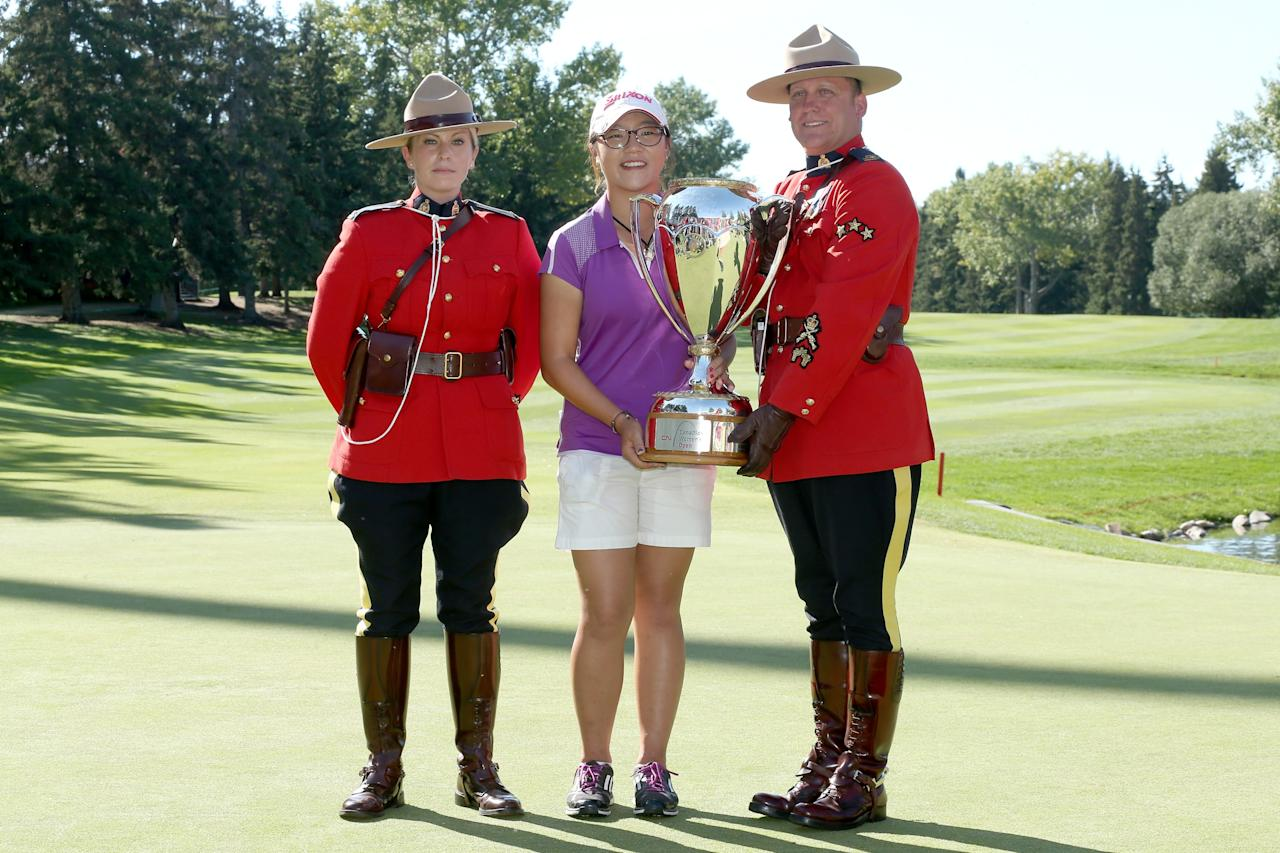 EDMONTON, AB - AUGUST 25: Lydia Ko of New Zealand poses with her trophy and two members of the Royal Canadian Mounted Police following her five stroke victory during the final round of the CN Canadian Women's Open at Royal Mayfair Golf Club on August 25, 2013 in Edmonton, Alberta, Canada. (Photo by Stephen Dunn/Getty Images)