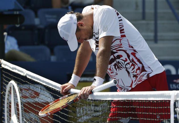 Ivan Dodig, of Croatia, leans on the net as he forfeits the match to Feliciano Lopez during the second round of the 2014 U.S. Open. (AP Photo/Kathy Willens)