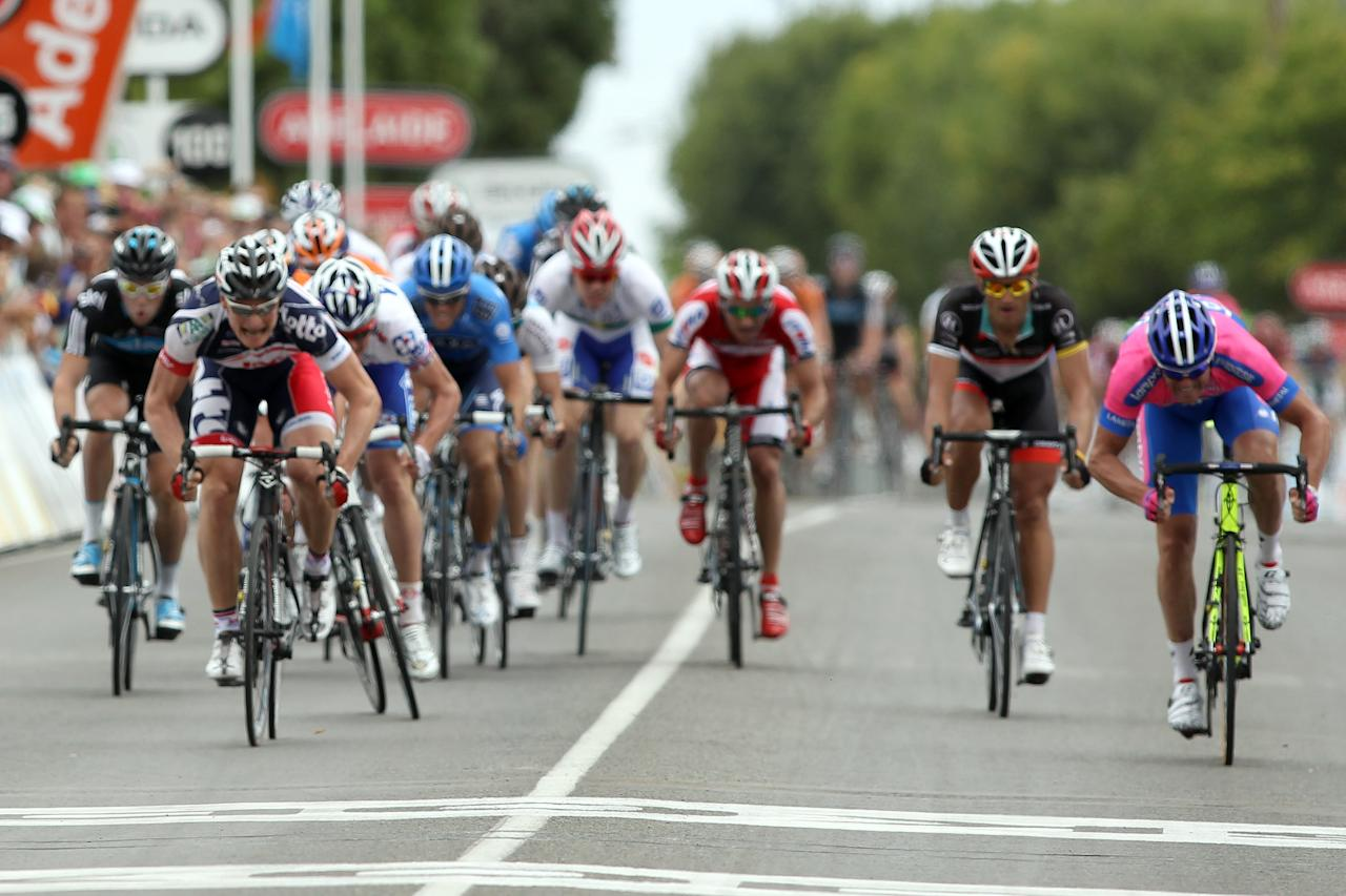 ADELAIDE, AUSTRALIA - JANUARY 17:  Andre Greipel (front left) of Germany and team Lotto-Belisol finishes the race first in a photo finish with Alessandro Petacchi (far right) of Italy and team Lampre-ISD during stage one of the 2012 Tour Down Under on January 17, 2012 in Adelaide, Australia.  (Photo by Morne de Klerk/Getty Images)
