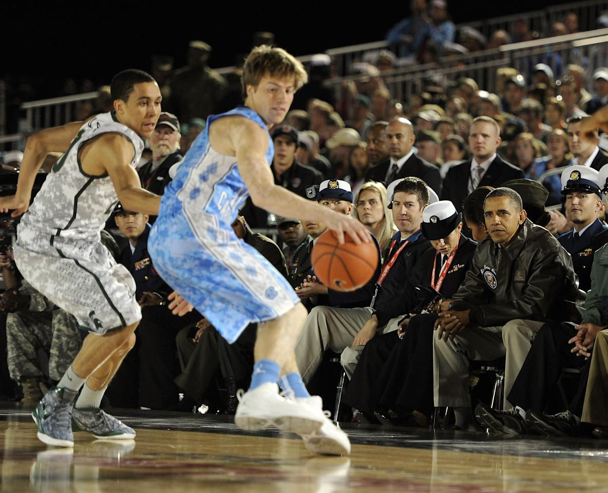 CORONADO, CA - NOVEMBER 11:  U.S. President Barack Obama watches Travis Trice #20 of the Michigan State Spartans guard Stilman White #11 of the North Carolina Tar Heels during the Quicken Loans Carrier Classic on board the USS Carl Vinson on November 11, 2011 in Coronado, California.  (Photo by Harry How/Getty Images)