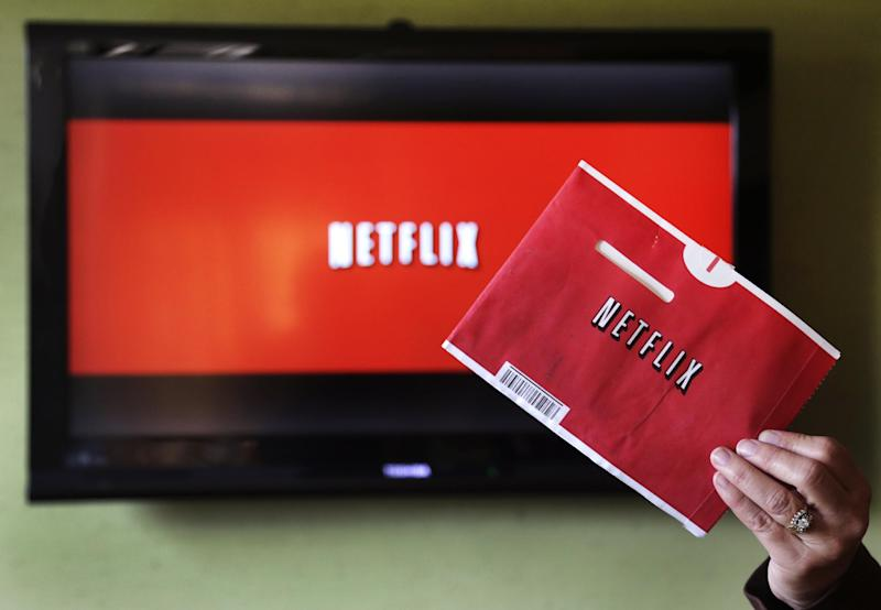 In this Tuesday, Oct. 23, 2012, photo, a woman holds up a Netflix envelope to be photographed in front of  a Netflix application on a television in East Derry, N.H.  Netflix slashed its prediction of how many U.S. video streaming subscribers it would add this year after subpar third-quarter results, causing a sharp sell-off in its stock in after-hours trading. The Los Gatos, California-based video streaming company said Tuesday it added 1.2 million net subscribers in the U.S. in the three months through September, which was on the low end of its previous forecast of gains between 1 million to 1.8 million. (AP Photo/Charles Krupa, File)