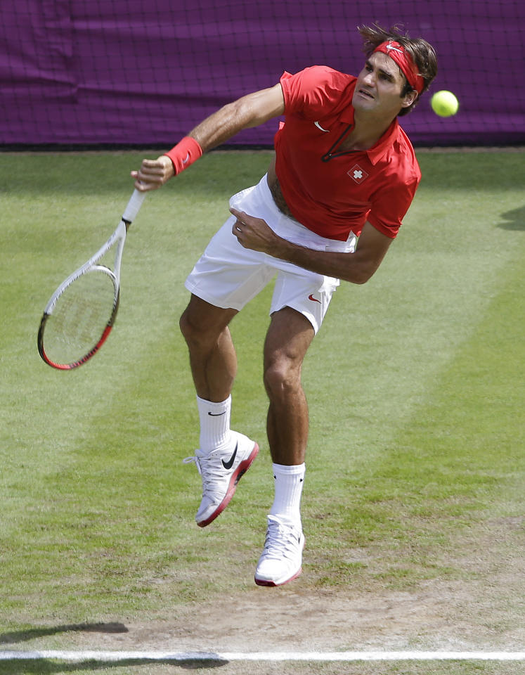 Roger Federer of Switzerland serves to Julien Benneteau of France at the All England Lawn Tennis Club in Wimbledon, London at the 2012 Summer Olympics, Monday, July 30, 2012. (AP Photo/Elise Amendola)