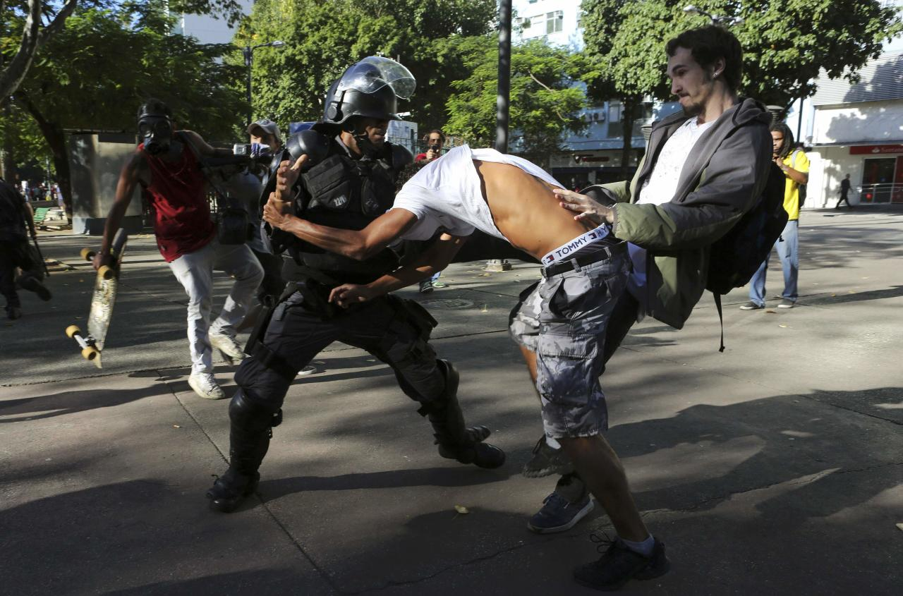 Demonstrators clash with a policeman before the World Cup final match between Argentina and Germany in Rio de Janeiro July 13, 2014. REUTERS/Nacho Doce (BRAZIL - Tags: SPORT SOCCER WORLD CUP POLITICS CIVIL UNREST)
