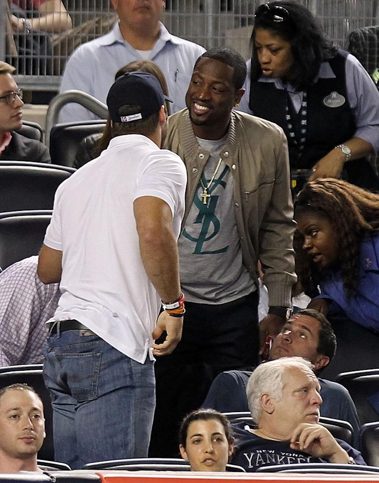 NEW YORK, NY - APRIL 15:  New York Jet quarterback, Tim Tebow and Miami Heat's Dwyane Wade talk in the stands during the game between the Los Angeles Angels of Anaheim and the New York Yankees  at Yankee Stadium on April 15, 2012 in the Bronx borough of New York City. In honor of Jackie Robinson Day, all players across Major League Baseball will wear number 42.  (Photo by Nick Laham/Getty Images)