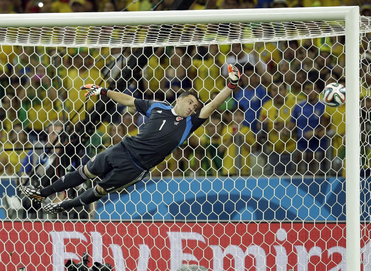 Colombia's goalkeeper David Ospina dives trying to stop a fee kick goal by Brazil's David Luiz during the World Cup quarterfinal soccer match between Brazil and Colombia at the Arena Castelao in Fortaleza, Brazil, Friday, July 4, 2014. (AP Photo/Hassan Ammar)