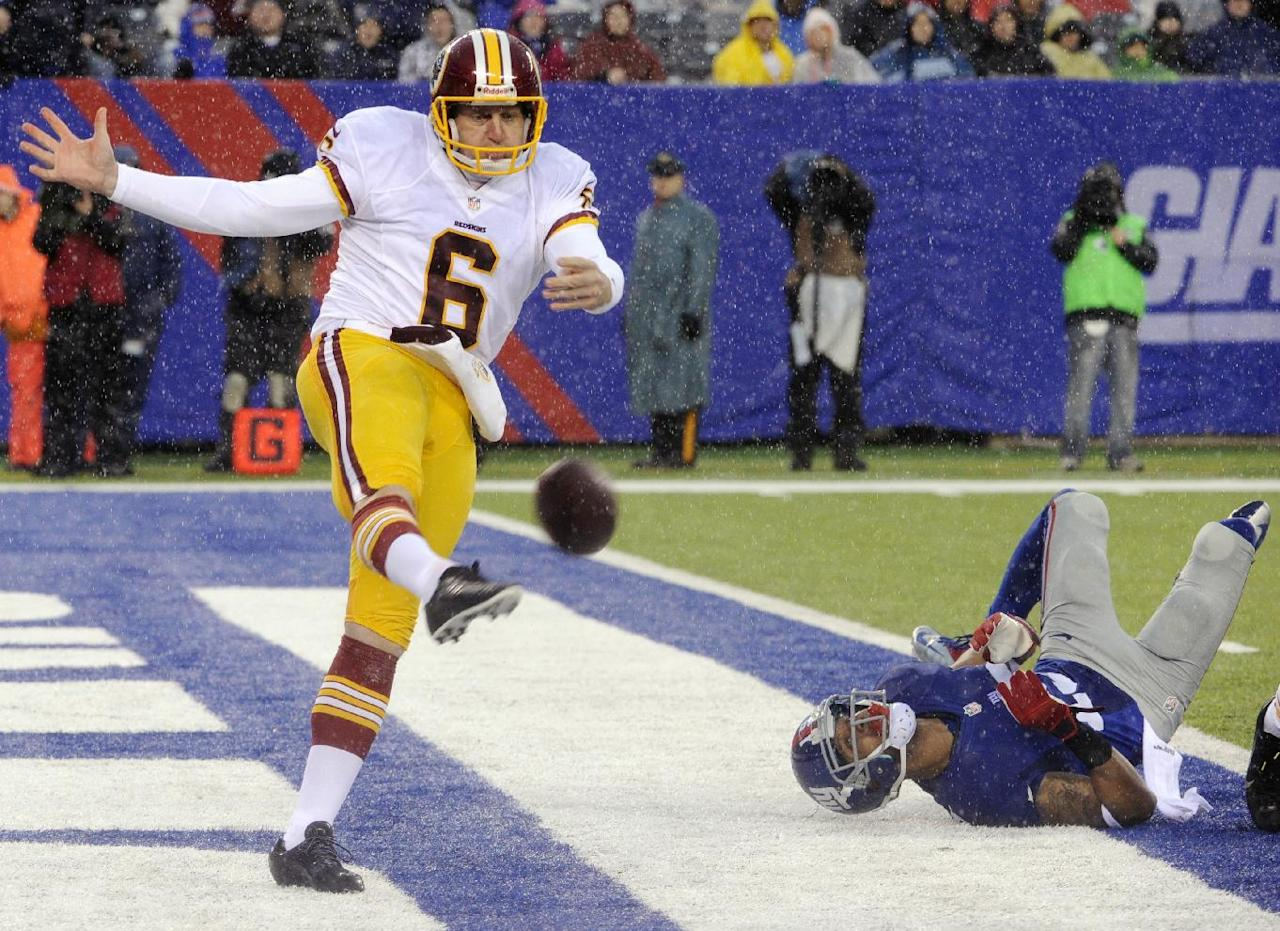 Washington Redskins punter Sav Rocca (6) kicks the ball away from New York Giants' Julian Talley (19) during the first half of an NFL football game on Sunday, Dec. 29, 2013, in East Rutherford, N.J. (AP Photo/Bill Kostroun)