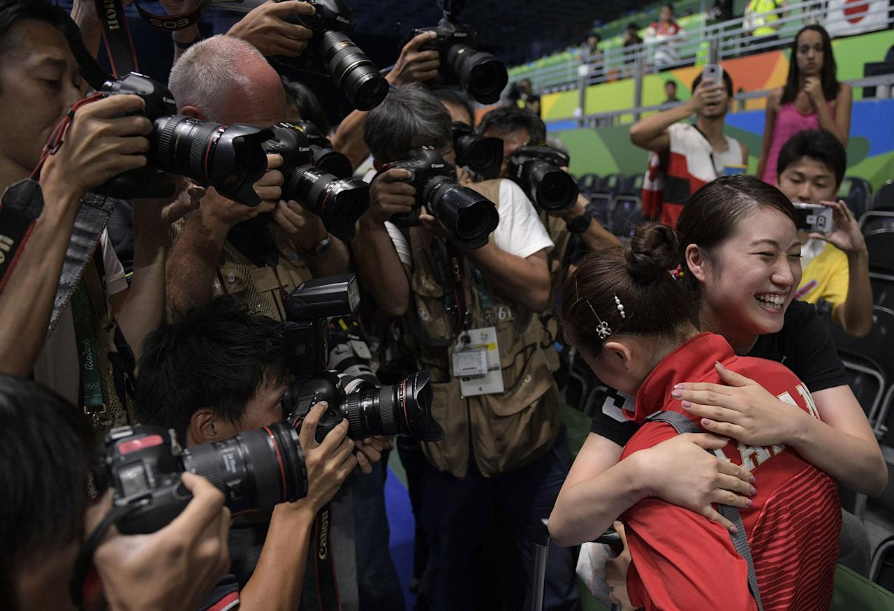 <p>Photographers gather around Japan's Ai Fukuhara (R) as she hugs a fan after winning the women's team bronze medal table tennis match against Singapore at the Riocentro venue during the Rio 2016 Olympic Games in Rio de Janeiro on August 16, 2016. (JUAN MABROMATA/AFP/Getty Images) </p>