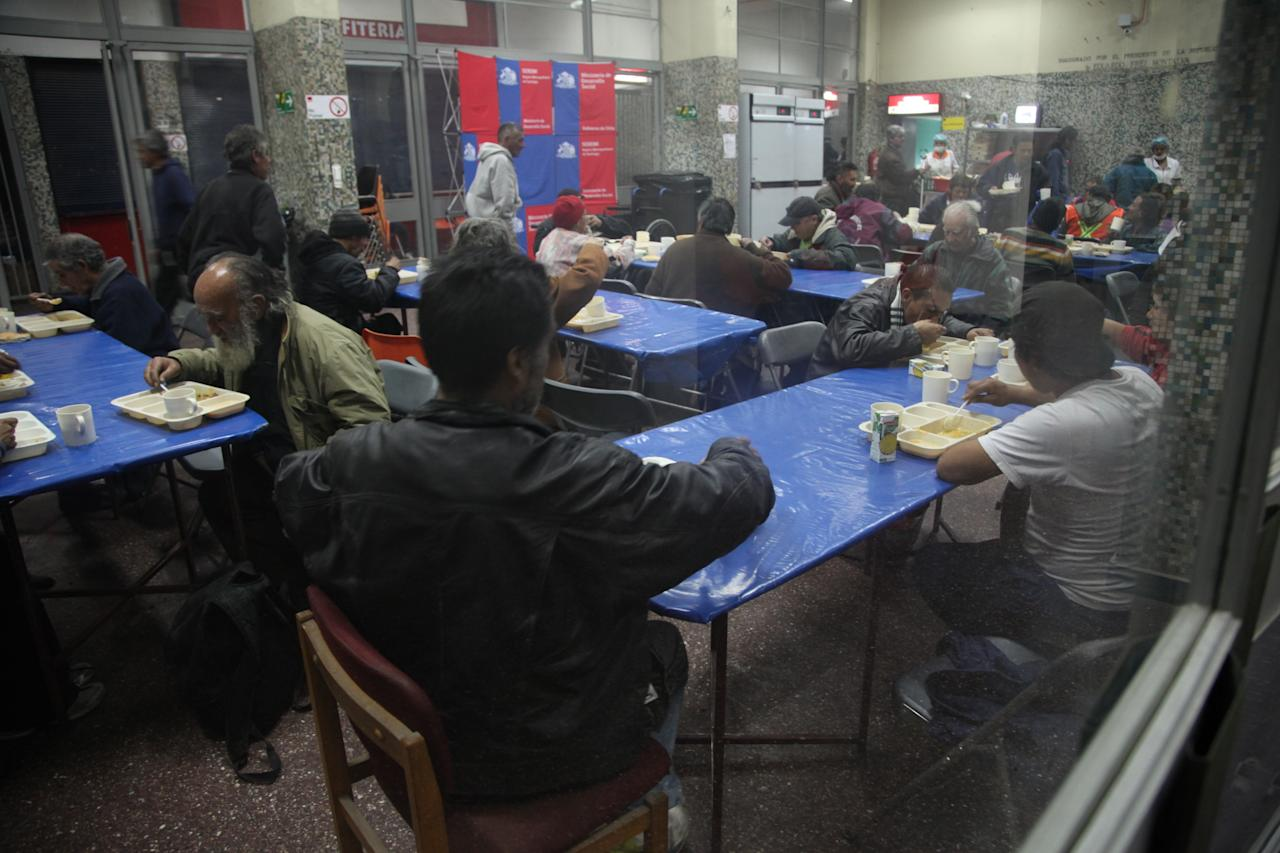 In this May 24, 2013 photo, people eat a hot dinner at the indoor stadium Estadio Victor Jara, which operates as a homeless shelter at night during the winter in Santiago, Chile. In the stadium that served as a torture facility 40 years ago, Santiago's most marginalized population can sleep indoors during Chile's biting winter. (AP Photo/Brittany Peterson)