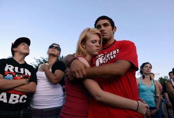 Lonnie Delgado (R) hugs Heaven Leek during a prayer for victims at the Century 16 movie theatre where a gunman attacked movie goers during an early morning screening of the new Batman movie, 'The Dark Knight Rises' on July 20, 2012 in Aurora, outside of Denver, Colorado. According to reports, 12 people were killed and 59 wounded when James Holmes allegedly opened fire inside the theater. Police have Holmes 24, of North Aurora, in custody. (Photo by Kevork Djansezian/Getty Images)